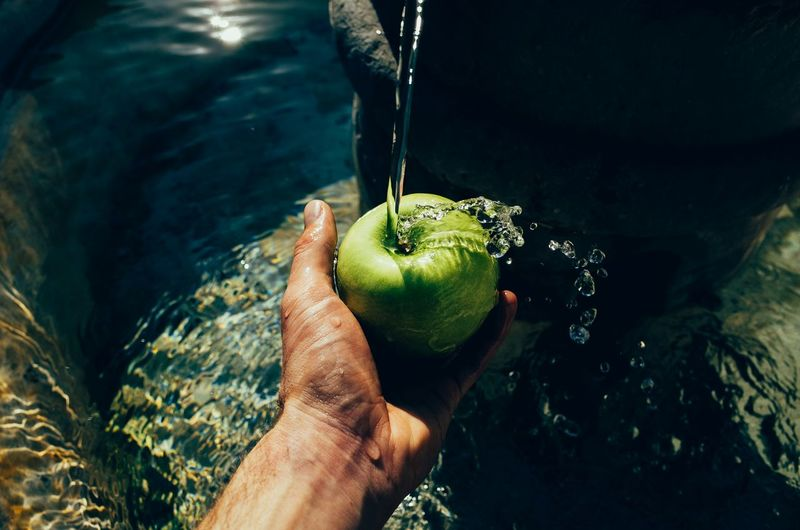 Cropped hand holding granny smith apple under flowing water at fountain