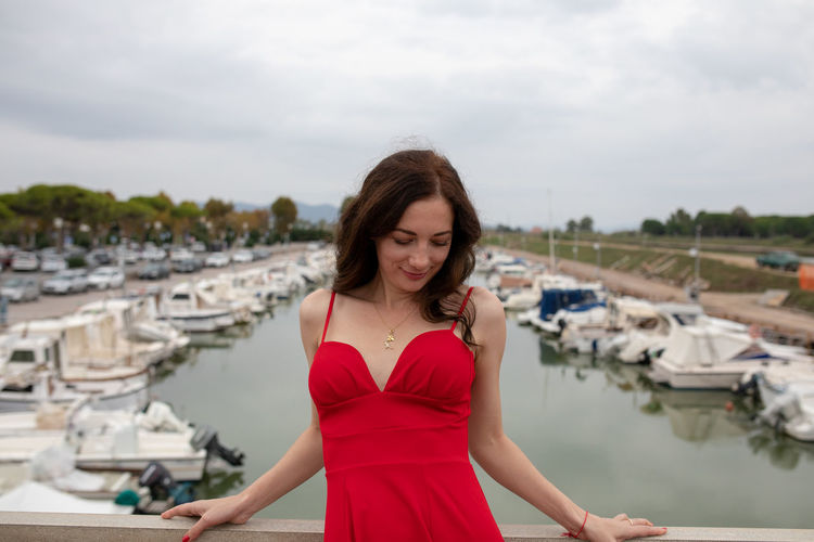 Woman wearing red dress while standing against boats moored at harbor