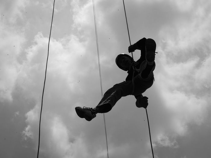 Low Angle View Of Man Zipplining Against Sky