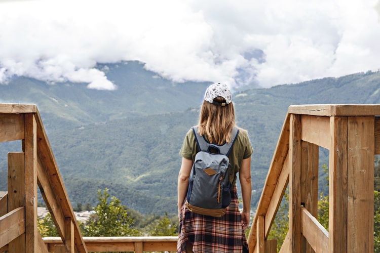 Rear view of woman in cap with backpacklooking at view of mountains and cloudy sky on viewpoint