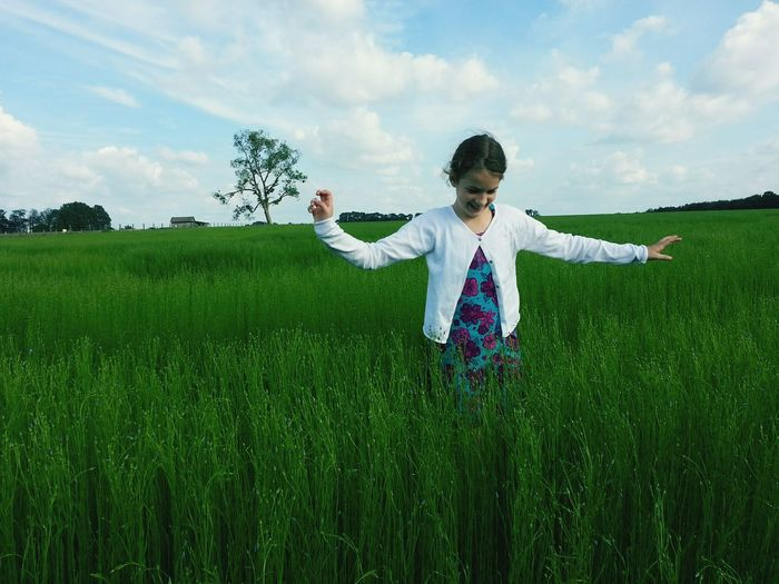 Playful Little Girl Walking Amidst Grass On Field Against Cloudy Sky