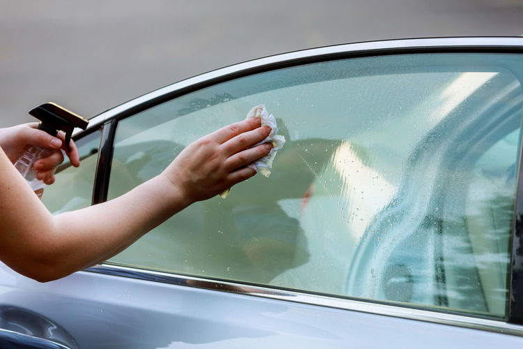 Cropped Hand Of Woman Cleaning Car Window