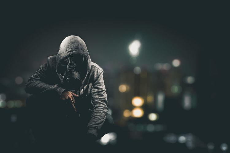 Man Wearing Gas Mask Crouching On Illuminated Street At Night