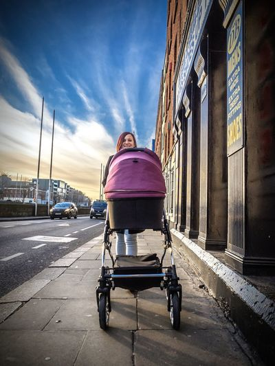 Smiling Woman With Baby Carriage Walking On Sidewalk In City Against Sky