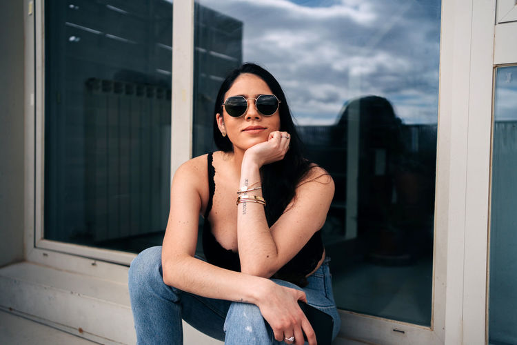 Young woman wearing sunglasses sitting by window
