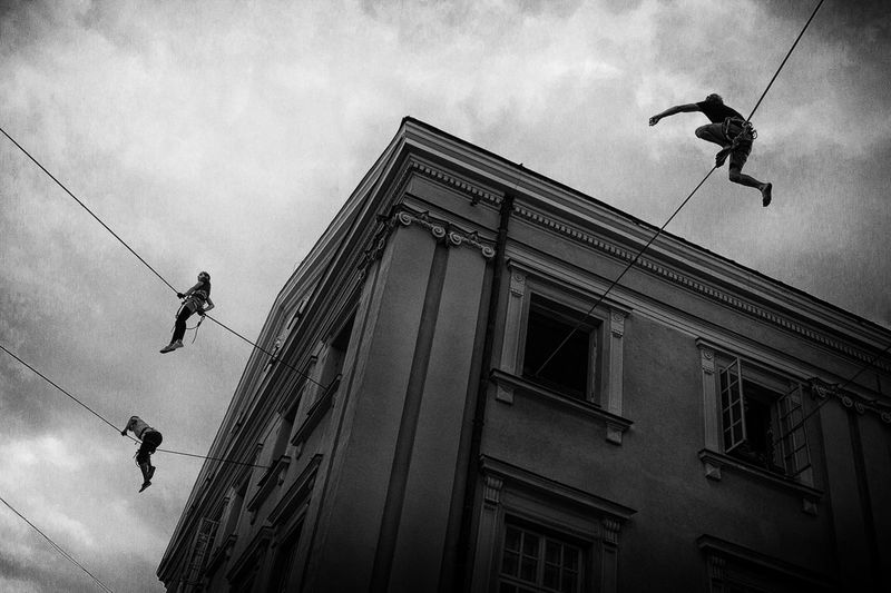 Adventure Architecture Building Exterior Built Structure Courage Danger Day Extreme Sports Full Length Hanging Lifestyles Low Angle View Manual Worker Men Occupation Outdoors Real People RISK Rope Skill  Sky Stunt Stunt Person Two People Window Washer