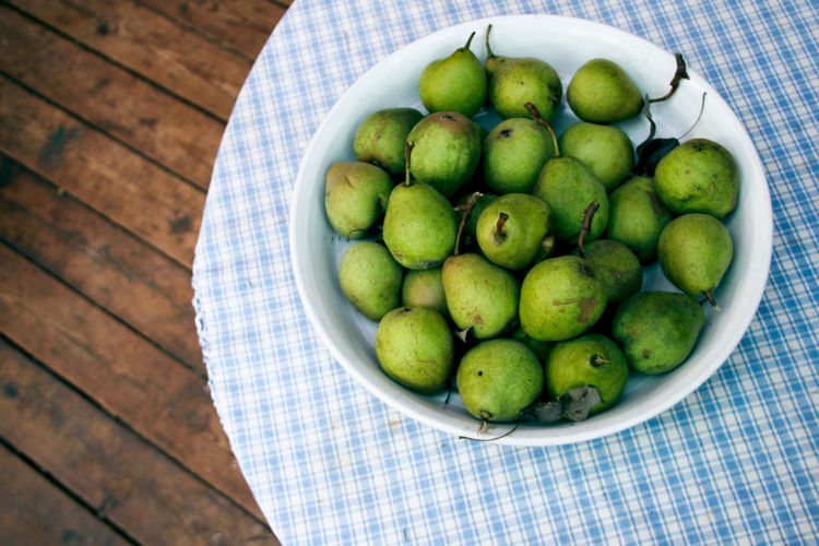High angle view of pears in bowl on place mat