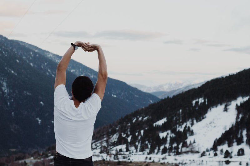 Rear view of man stretching arms against snowcapped mountain
