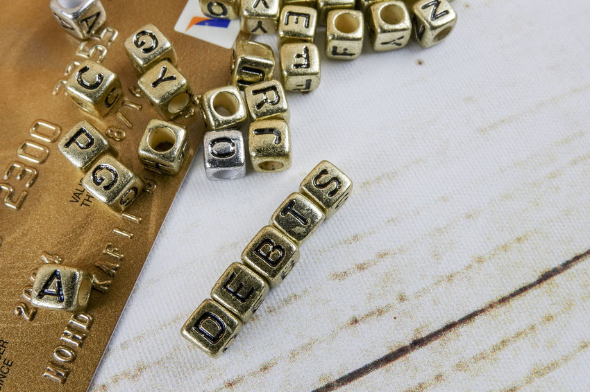 DEBT CONCEPT WITH GOLD DICE ON A WOODEN TABLE Credit Card Debt Crisis