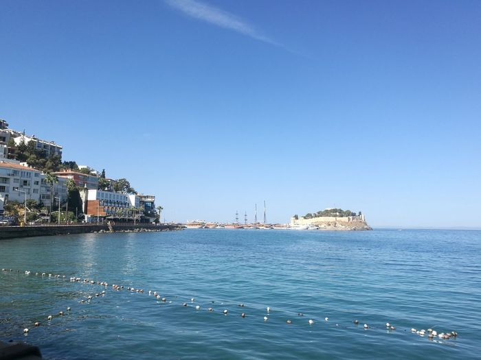 Scenic view of sea by buildings against clear blue sky