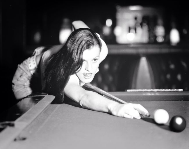 Young woman aiming ball at pool table