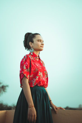 Woman looking away while standing against sky