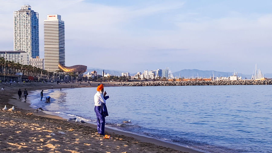 Beach Sea Full Length One Person Vacations Sky Sand Water People Travel Destinations Skyscraper Architecture Urban Skyline Cityscape City Built Structure Barcelona Mood Captures Beton_vs_nature Travel Barcelona, Spain Barcelonalove Streetphotography Portrait Portrait Of A Stranger