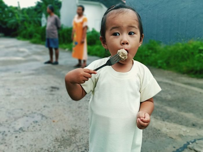 Baby girl having food while standing on road