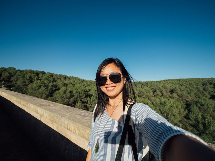 Portrait of smiling woman against clear blue sky