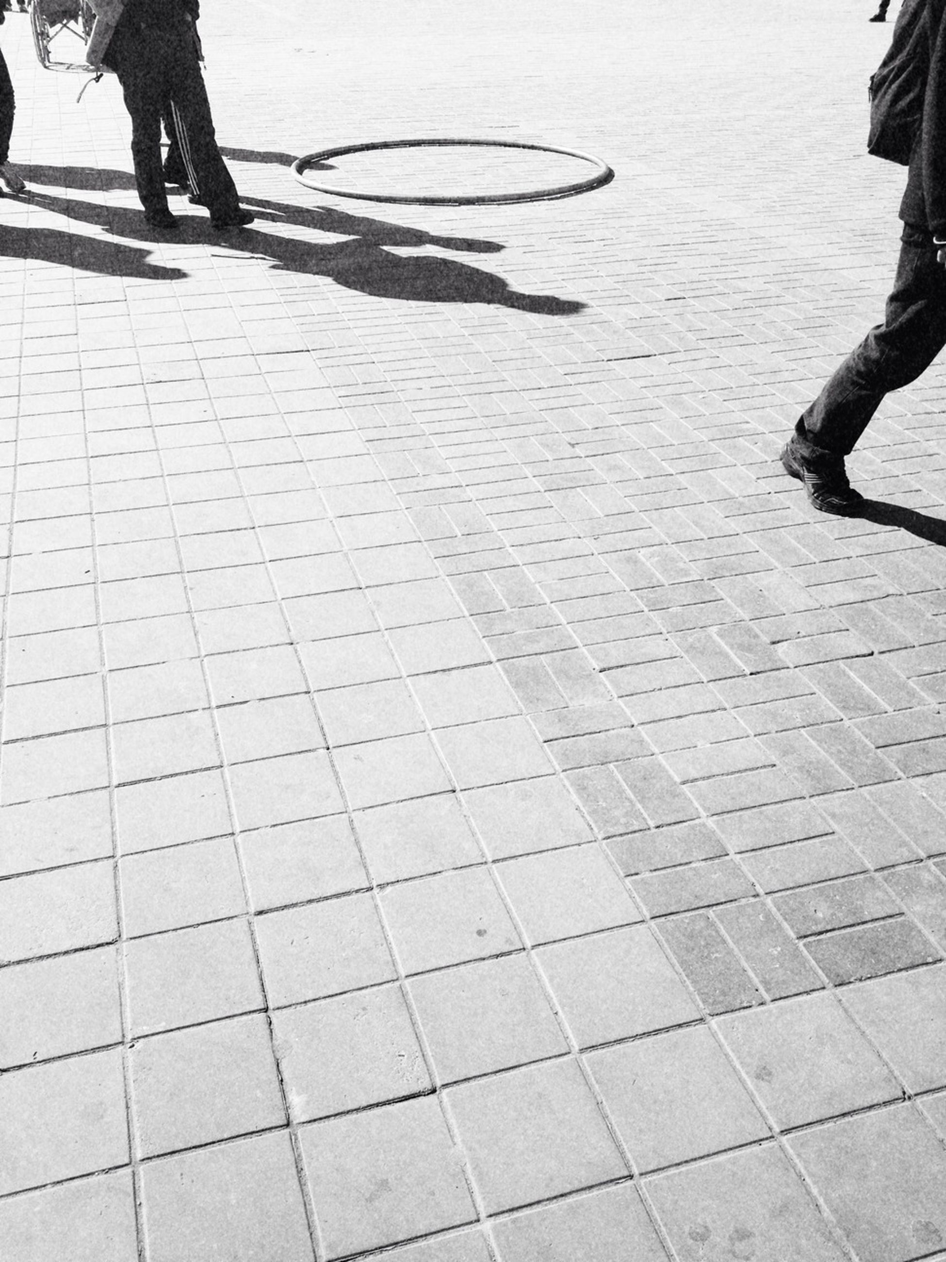 low section, person, lifestyles, men, walking, leisure activity, paving stone, cobblestone, tiled floor, standing, shadow, footpath, street, human foot, unrecognizable person