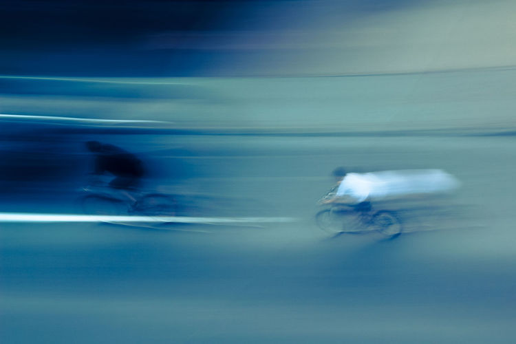 Blurred motion of people riding in blue water
