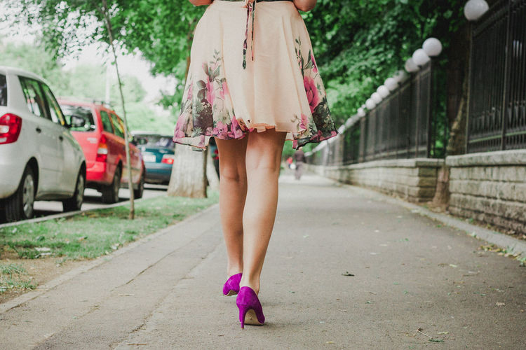 Low section of woman walking on road