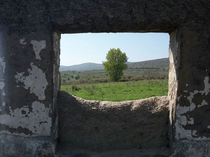 Close-up of abandoned window on field against sky