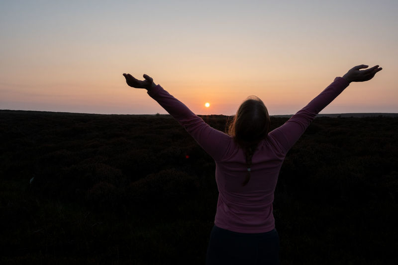 Rear view of woman with arms raised standing against sky during sunset