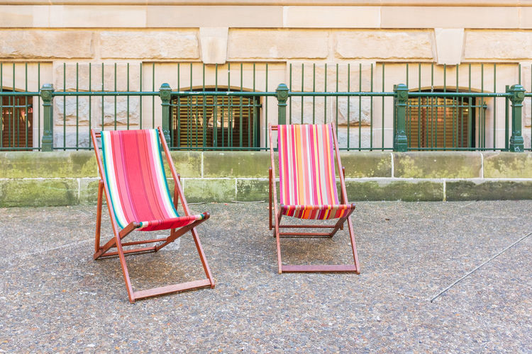 Colourful deckchairs Seat Chair Architecture Day Empty Absence No People Built Structure Building Exterior Nature Building Outdoors Relaxation Deck Chair Red Sunlight Wood - Material Land House Wall Foldable Outdoor Chair