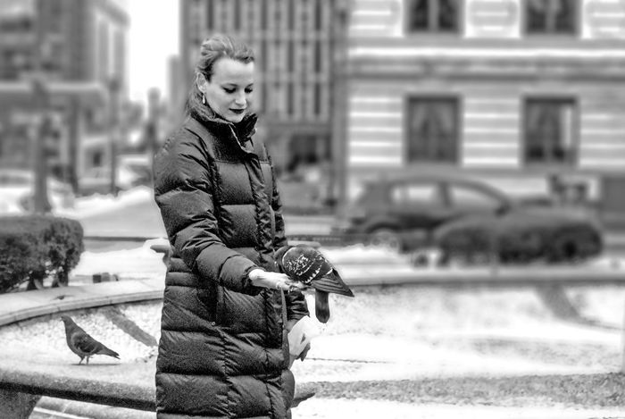 Adult Bird Black And White Caring City Coat Cold Feeding  Flight Flock Fly Full Length Hand Lifestyles Monochrome Palm Party Pigeons Real People Sidewalk Trust Urban Winter Woman Young
