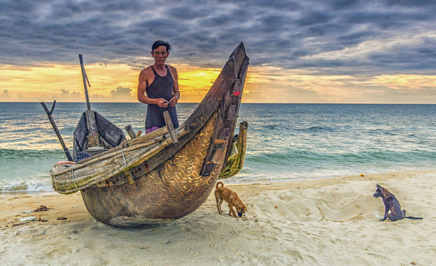 fisherman and two dogs Longtail Boat Men Real People Sea Sky Sunset Water