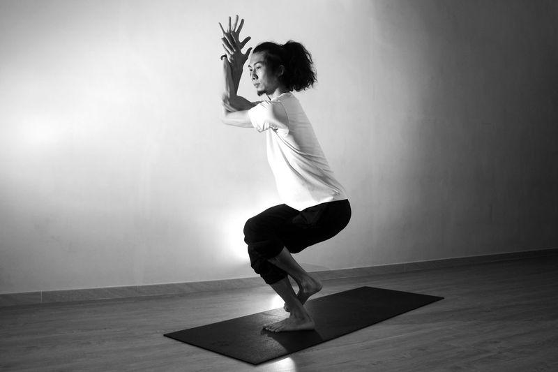 Full length of man exercising on mat against wall