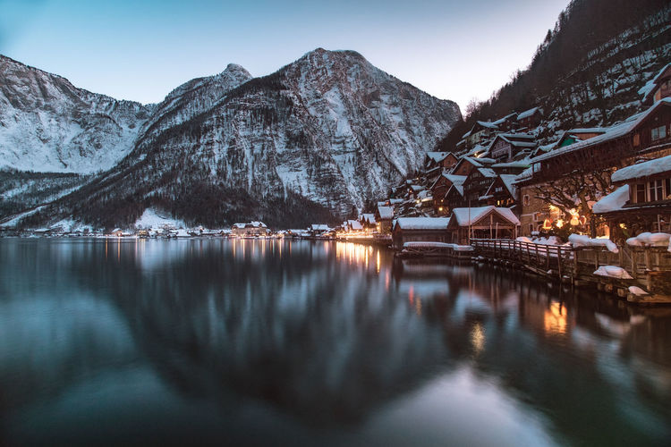 Snowcapped mountain and houses reflecting on lake in town