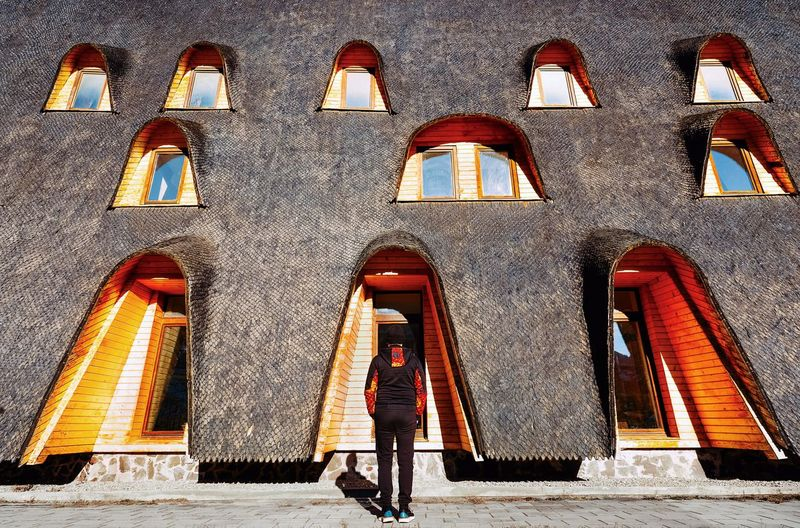 Full length rear view of man standing against traditional building