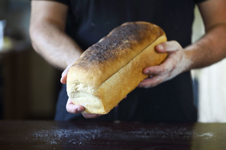 Midsection of man holding bread