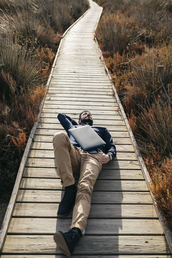 High Angle View Of Mid Adult Man With Laptop Lying On Boardwalk