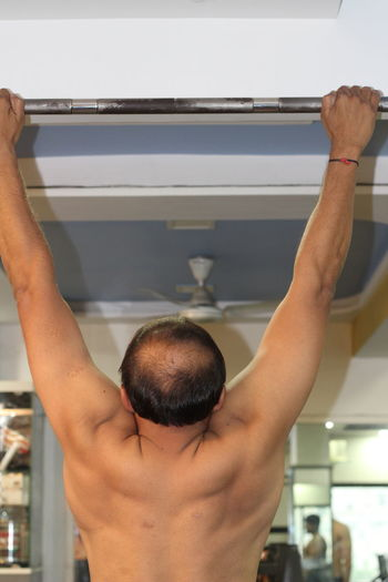 Close-Up Rear View Of Man Doing Pull Ups