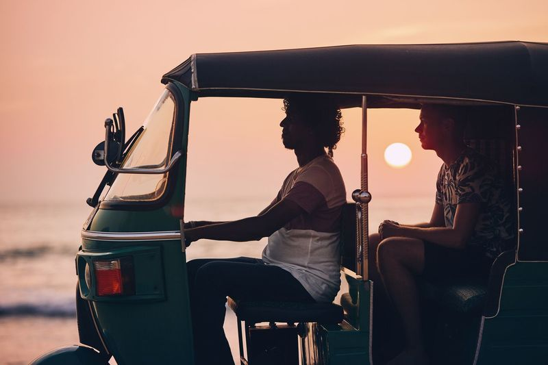 Driver and passenger are traveling by tuk tuk taxi against sea at sunset in Sri Lanka. TukTuk Taxi Driver Driving Passenger Adventure Vacations Journey Customer  Men Two People Tourism Tourist Sri Lanka Travel Transportation Sun Sunset Moody Sky Business Sea Nature Young Men Road Trip Freedom