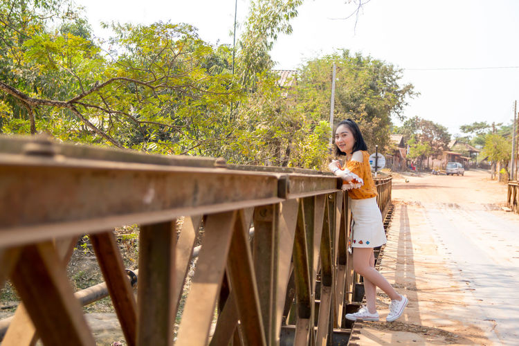 Portrait of young woman standing on bridge against trees