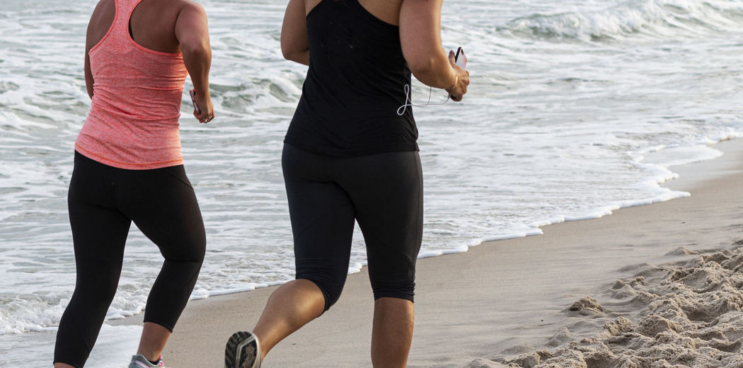Midsection of women running on beach
