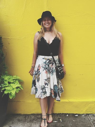 Full length of happy woman standing against yellow wall