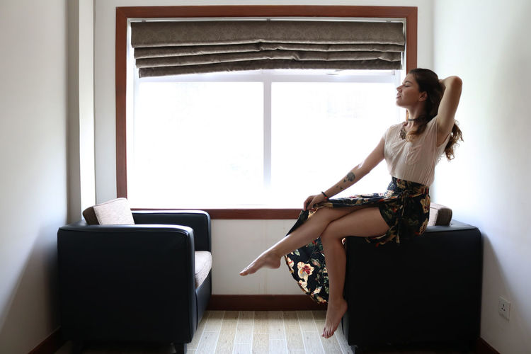 Young woman looking at camera while sitting on window