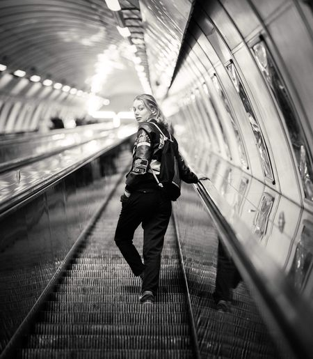 Full Length Portrait Of Woman Standing On Moving Walkway