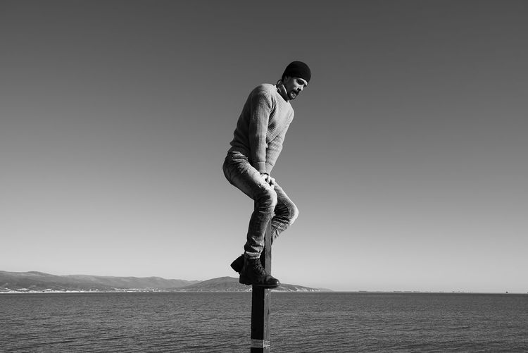 A young man does something interesting. It interacts with a wooden pile on the seashore. One person in the frame. Man on the background of a clear sky. He is warmly dressed in boots, jeans, a sweater and a hat. Casual wear. The guy wears a mustache and stubble. Hair out of the caps. Winter sunny day. Live black and white photo. Lifestyles Lifestyle Authentic Moments Authentic Candid Real People Blackandwhite Black And White Full Length One Person Sky Clear Sky Water Tranquil Scene Leisure Activity Nature Side View Scenics - Nature Beauty In Nature Land Copy Space Casual Clothing Standing Tranquility Motion