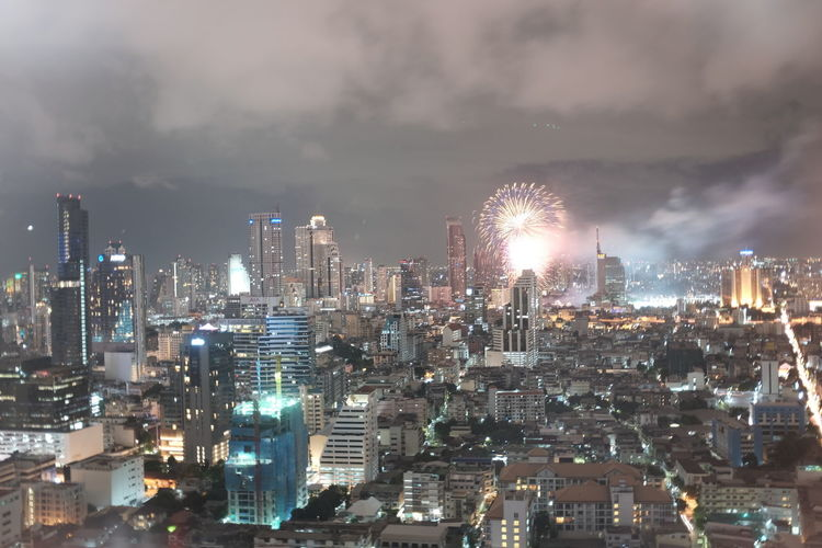 Firework exploding over illuminated cityscape against sky