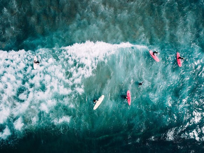 Aerial view of people surfboarding on sea