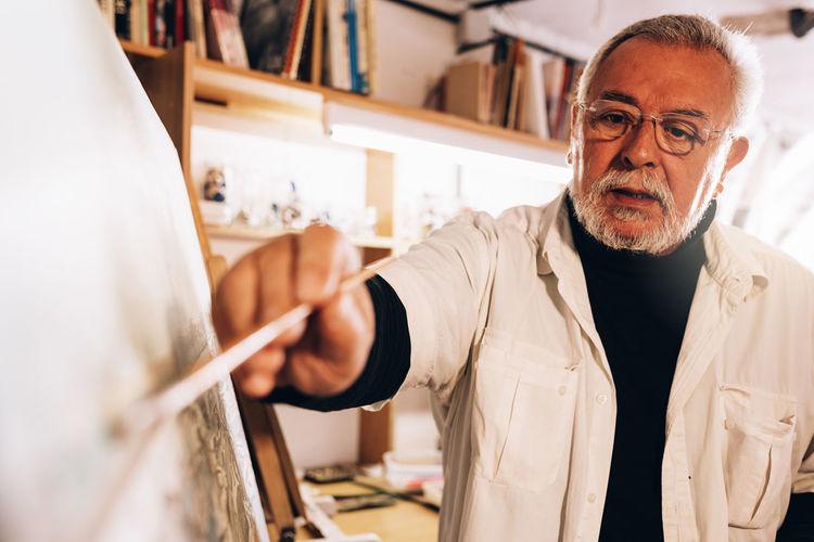 Mature man painting on canvas