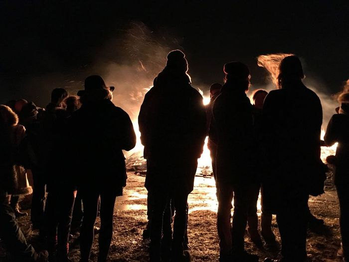 Silhouette people standing against bonfire at night