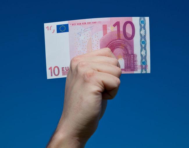 Hand holding ten euro note Blue Sky Bonus Euro Euro Notes Financial Financial Planning Financial Service Money Money Money Money Premium Ten Euro