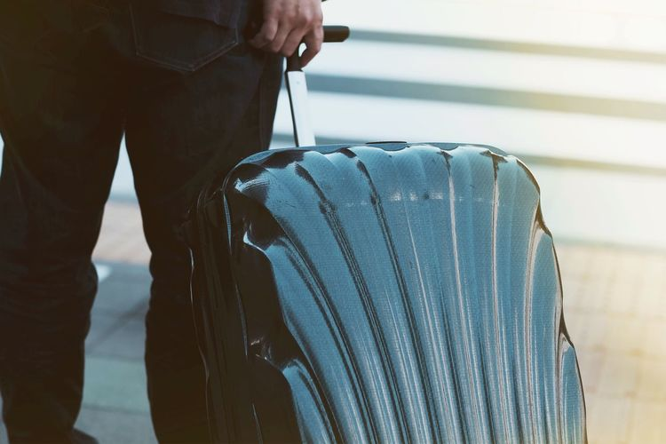 Midsection of businessman carrying suitcase on floor