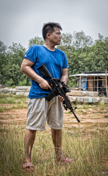 Men wearing blue T-shirts with guns ready to fire Adult Aggression  Casual Clothing Concentration Day Front View Full Length Grass Holding Leisure Activity Looking Looking Away Men Nature One Person Plant Sport Standing Tree Young Adult
