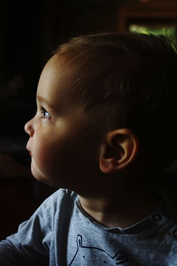 Close-up of cute baby boy looking away