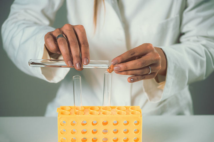 Midsection of female scientist experimenting in laboratory