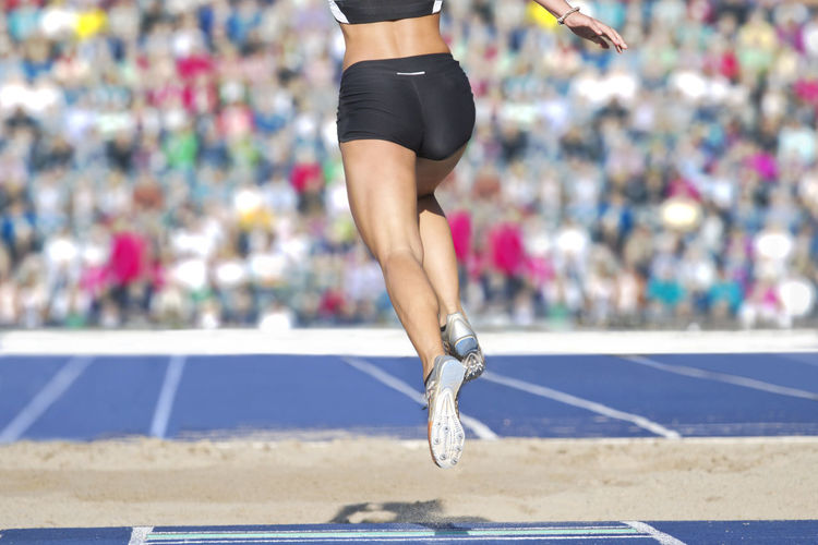 Low section of female athlete running on track